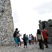 Erice a 750 metri sul monte omonimo, offre una vista spettacolare sulla città di Trapani e le Isole Egadi a nord ovest della costa siciliana..Un gruppo di turisti escono dal castello di Venere a Erice   ..Erice is located on top of Mount Erice, at around 750m above sea level, overlooking the city of Trapani and the Aegadian Islands on Sicily's north-western coast, providing spectacular views..A tourists group go out from Castle of Venus.
