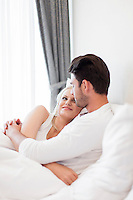 Romantic young couple embracing in bed