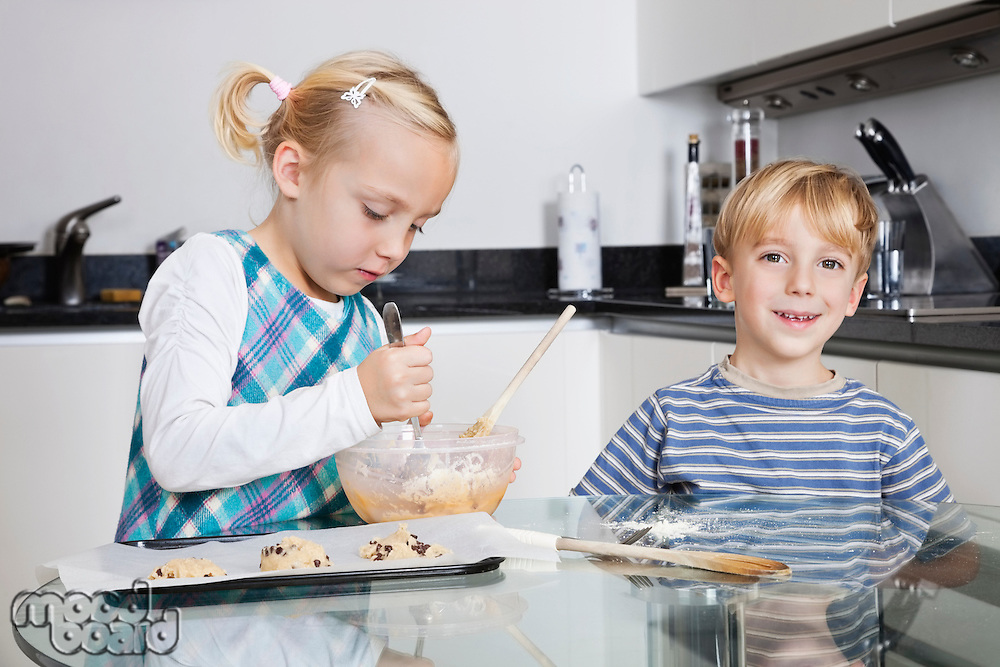 Happy brother and sister baking cookies in kitchen