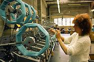 Woman operating a machine winding wool into skeins . Robin Wools Ltd also known as Robert Glew Wool Industries Ltd