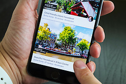 Airbnb holiday room booking app showing house boat in Amsterdam for rent on an iPhone 6 plus smart phone
