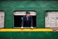 Portrait of a vietnamese man leaning out a train window, Hanoi, Vietnam, Southeast Asia