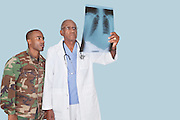 Senior doctor with US Marine Corps soldier looking at x-ray report over light blue background