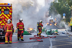 © Licensed to London News Pictures. 21/09/2019. Paris, France. Firefighters put out fires lit on the street as protesters clash with police at a climate change demonstration in Paris. Photo credit: Peter Manning/LNP