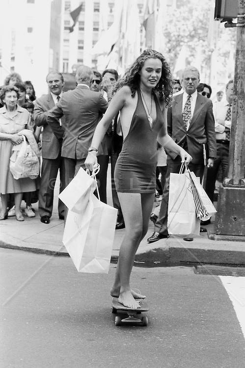 Female Skateboarder in New York City in short shirt and holding shopping bags