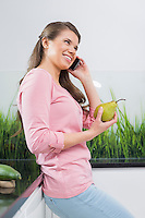 Happy woman using cell phone while holding pear in kitchen