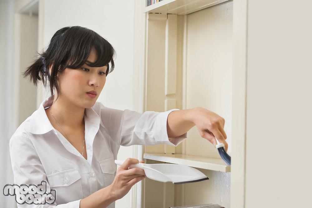 Female housekeeper cleaning shelf