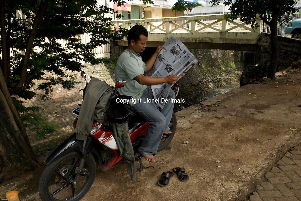 "Ojek (taxi-motorbike) driver takes a break reading his paper. Chauffeur de ""ojek"" (moto-taxi) lisant son journal."