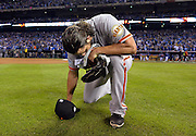 San Francisco Giants pitcher and World Series MVP Madison Bumgarner kneels to the ground after the final out against the Kansas City Royals in game 7 of the 2014 World Series.