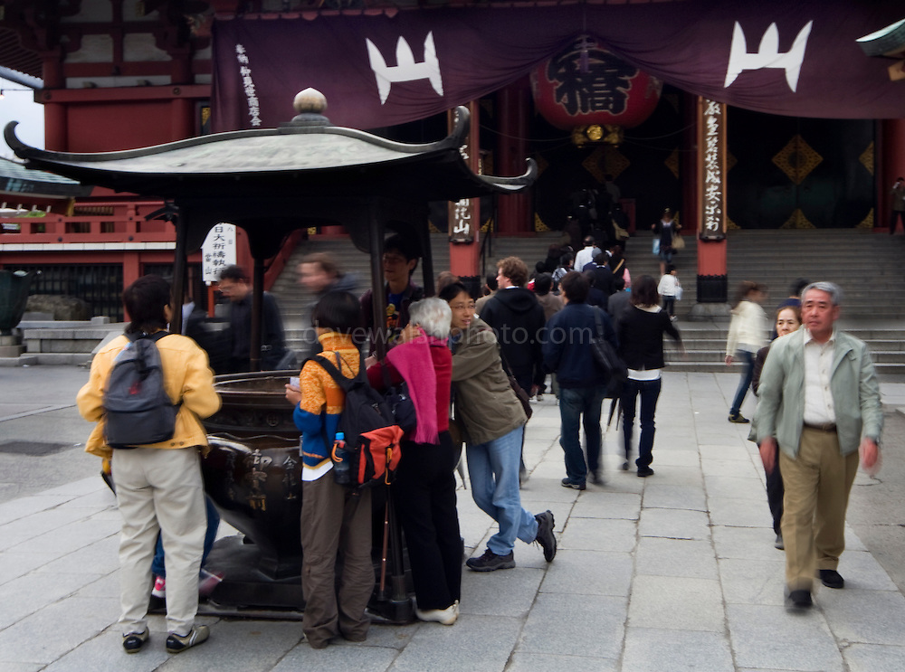 Pilgrims at the Seno-ji temple, Asakusa, cleaning their hands in smoke before entering the temple..