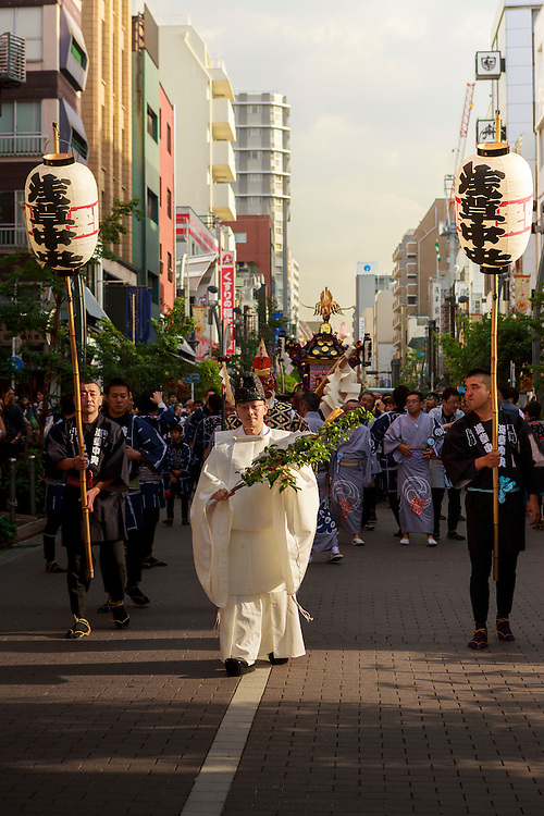 A Shinto priest leads the procession through the streets in a religious festival over a millenia old. Sanja Matsur (Three Shrine Festival), is an annual Shinto festival held in Tokyo. The earliest form of the festivals dates back to the 7th century CE and is held in honor of Hinokuma Hamanari, Hinokuma Takenari and Hajino Nakatomo, the three men who established and founded Sensō-ji temple. Sanja Matsuri is held on the third weekend of every May at Asakusa Shrine. Its  parades revolve around three mikoshi (three portable shrines referenced in the festival's name), as well as traditional music and dancing.