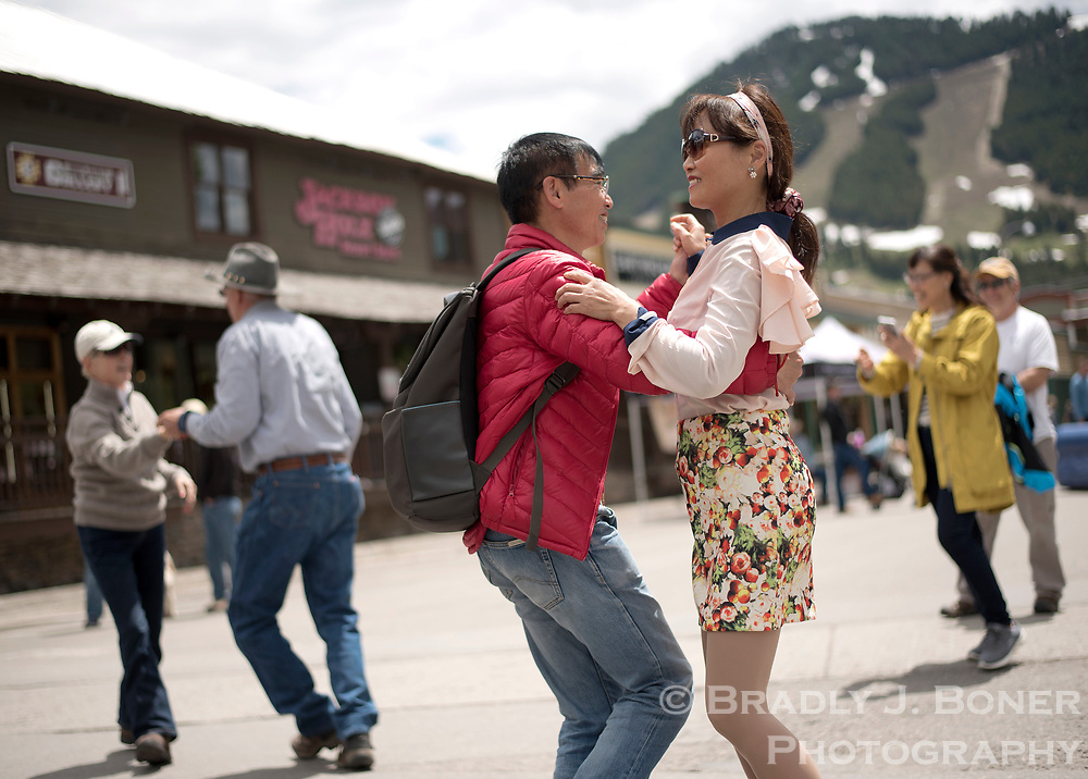 Tourists dance to the live music regaling the Old West Days crowd Saturday at the Jackson Town Square.