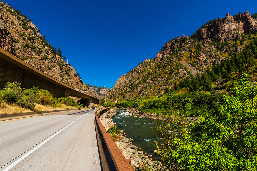 Interstate 70 passing through the 12.5 mile long Glenwood Canyon, near Glenwood Springs, Colorado USA. The road, which includes elevated portions, is a marvel of engineering. The gorge was carved by the Colorado River, which is seen on the right. The canyon is considered to be one of the most scenic natural features of the Interstate Highway system in the U.S. It took 13 years to build and opened in 1992. the most scenic natural features of the Interstate Highway system in the U.S. It took 13 years to build and opened in 1992.