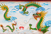 "12 APRIL 2012 - HO CHI MINH CITY, VIETNAM:   A relief of a Chinese dragon in Chùa Quan Âm (Avalokiteshvara Pagoda), a Chinese style Buddhist pagoda in Cho Lon. Founded in the 19th century, it is dedicated to the bodhisattva Quan Âm. The pagoda is very popular among both Vietnamese and Chinese Buddhists. Cholon is the Chinese-influenced section of Ho Chi Minh City (former Saigon). It is the largest ""Chinatown"" in Vietnam. Cholon consists of the western half of District 5 as well as several adjoining neighborhoods in District 6. The Vietnamese name Cholon literally means ""big"" (lon) ""market"" (cho). Incorporated in 1879 as a city 11 km from central Saigon. By the 1930s, it had expanded to the city limit of Saigon. On April 27, 1931, French colonial authorities merged the two cities to form Saigon-Cholon. In 1956, ""Cholon"" was dropped from the name and the city became known as Saigon. During the Vietnam War (called the American War by the Vietnamese), soldiers and deserters from the United States Army maintained a thriving black market in Cholon, trading in various American and especially U.S Army-issue items.        PHOTO BY JACK KURTZ"