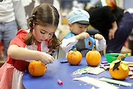 Middletown, New York - Two children wearing costumes decorate pumpkins at the Family Fall Festival at the Middletown YMCA on Oct. 23, 2010. ©Tom Bushey / The Image Works