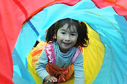 Julisa Salazar, 3, has fun crawling through this colorful play tunnel at Sunday's Dia Del Niño Event at La Paz Park in Salinas. The family event, co-sponsored with Poder Popular, drew children and their parents from all over the community to enjoy music, food and games from 11:00 AM to 4:00 PM.
