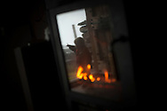 Oihu, reflected on the fires glass, shows the rain. Brontallo (Switterland) July 02, 2014. Beñat and Nathalie spend two months (July and August) on Spulüi, at 1.900 meters, taking care of goats and making cheese. Their children Kemen (7 years old) and Oihu (18 months) are with them. (Gari Garaialde / Bostok Photo)