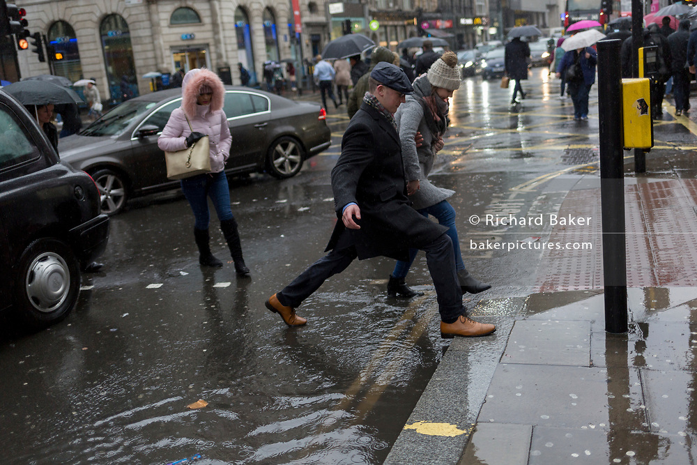 London, 24th January 2018: Storm Georgina swept across parts of Britain and in central London, lunchtime office workers were caught out by torrential rain and high winds. Pedestrians resorted to leaping across deep puddles at the junction of New Oxford Street and Kingsway at Holborn. Credit: Richard Baker / Alamy Live News.
