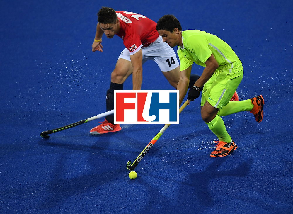 Brazil's Bruno Bitencourt controls the ball as Britain's Mark Gleghorne chases during the men's field hockey Brazil vs Britain match of the Rio 2016 Olympics Games at the Olympic Hockey Centre in Rio de Janeiro on August, 9 2016. / AFP / MANAN VATSYAYANA        (Photo credit should read MANAN VATSYAYANA/AFP/Getty Images)
