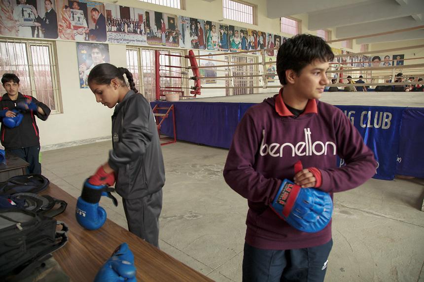 Trois jeunnes filles se preparent pour la session d'entraînement de boxe, dans le gymnase du Bhiwani Boxing Club