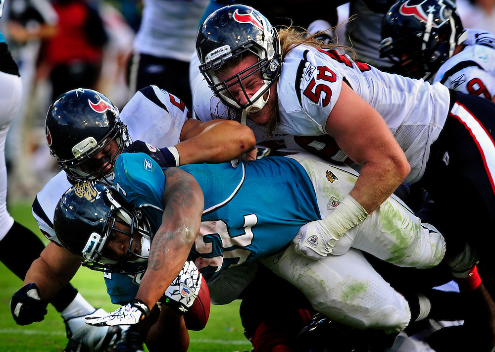 Jacksonville Jaguars running back Maurice Jones-Drew (32) is tackled by Houston Texans outside linebacker Brooks Reed (58)during the fourth quarter of an NFL football game, Sunday, Nov. 27, 2011, in Jacksonville, Fla. The Texans beat the Jaguars 20-13. (AP Photo/Stephen Morton)