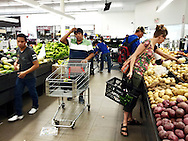 Several male migrant workers shop at Freshco in Leamington. The workers usually shop in large numbers on Fridays and the weekend. The store makes an effort to supply foods and products the largely Hispanic and Caribbean groups may like such as many varieties of peppers and cheeses. Nicole Noel, the woman in the photo, is a long time social justice activist and university staff member.