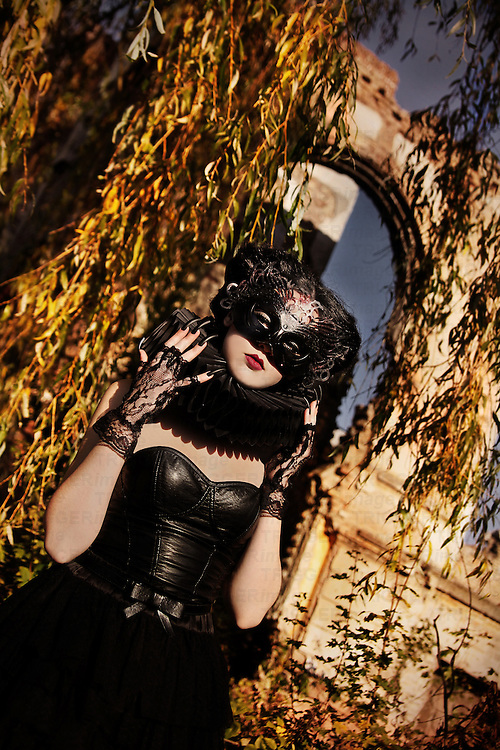 A girl wearing a mask and dressed in black standing in front of castle ruins and trees in autumnal colors.