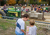 Richard and Bowden Coombs of Rye share a box of popcorn while they watch the tractor pulling at the Sandwich Fair on Saturday.  (Karen Bobotas/for the Laconia Daily Sun)