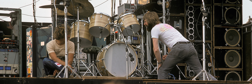"""Phil Lesh and Ram Rod in conversation on stage before the Grateful Dead Play Live at Dillon Stadium, Hartford, CT 31 July 1974. Featuring the Wall of Sound. Summer weekday show, one of the longest ever played by The Dead. Deadheads hanging out, Crew setting up. Cropped for panoramic, example: 10x30"""", prints."""