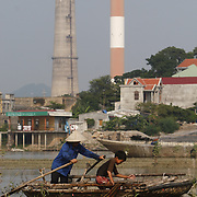 A fisherman and young boy bring in their catch outside the coal-powered electricty plant in Phai Lai, about 70 kilometers east of Hanoi, Vietnam, 14 September, 2007.
