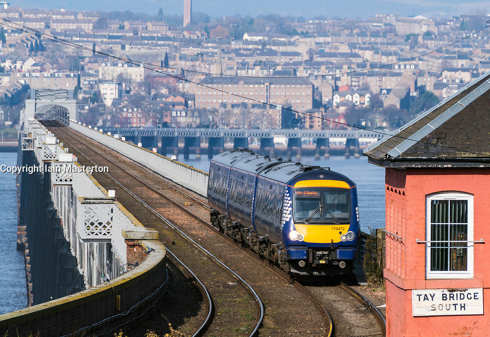 View of Scotrail diesel passenger train travelling from Dundee across the Tay Rail Bridge at Wormit in Tayside, Scotland, United Kingdom