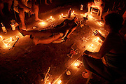 """Velatione"" on a Chilean patient in Quiballo, near the holy mountain of Sorte, Venezuela. The ""Velatione"", from the Spanish ""vela"", meaning candle, is a cure, purification and energy recharge rite. The patient lays on an ""oracolo"", a drawing on the ground with esoteric symbols, made with talcum and surrounded by candles and fruit. She is then sprinkled with spirits and flower petals while three or four persons around her convey energy. The body is shaken with shivers, contracting spontaneously and uncontrollably."