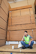 Pensive female industrial worker sitting cross-legged on wooden planks