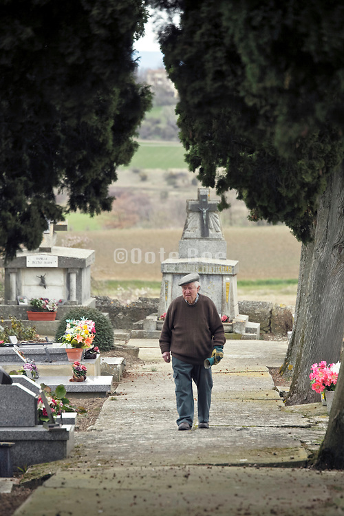 elderly man walking and maintaining family graveyard