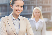 Portrait of happy young businesswoman with female colleague in background