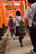 Tourists pass through the tori gates at Fushimi Inari, Kyoto.
