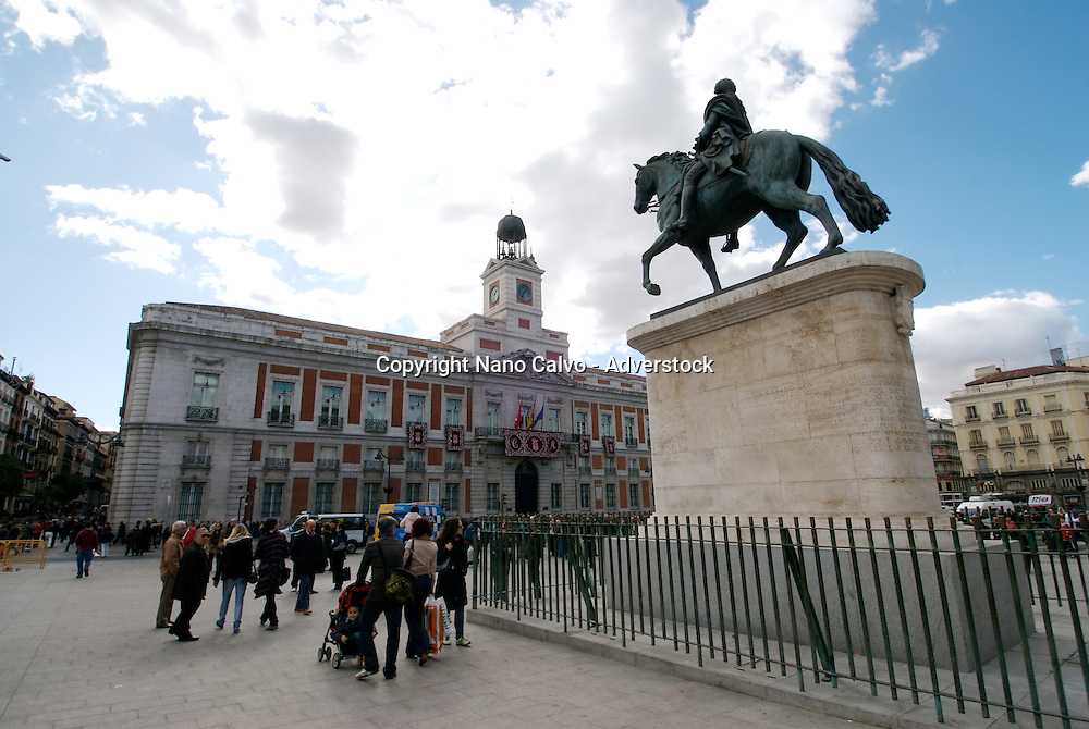 """Puerta del Sol (Spanish for """"Gate of the Sun"""") is one of the most well known and busiest places in Madrid. This is the centre (Km 0) of the radial network of Spanish roads. The square also contains the famous clock whose bells mark the traditional eating of the Twelve Grapes and the beginning of a new year. The New Year's celebration has been broadcast live on TV since 31 December 1962"""