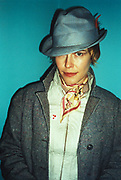 Club portrait of woman wearing blue top hat, small satin scarf and heavy grey jacket, London, U.K, 2000.