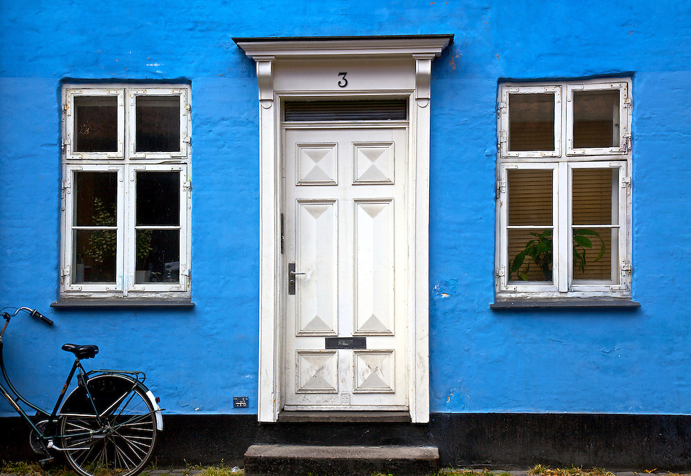 A brightly colored blue house with bicycle in front stands out in the heart of Copenhagen, Denmark
