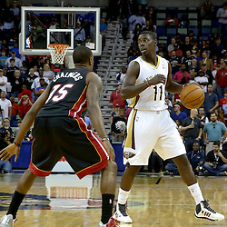Oct 23, 2013; New Orleans, LA, USA; New Orleans Pelicans point guard Jrue Holiday (11) is guarded by Miami Heat point guard Mario Chalmers (15) during the first half of a preseason game at New Orleans Arena. Mandatory Credit: Derick E. Hingle-USA TODAY Sports