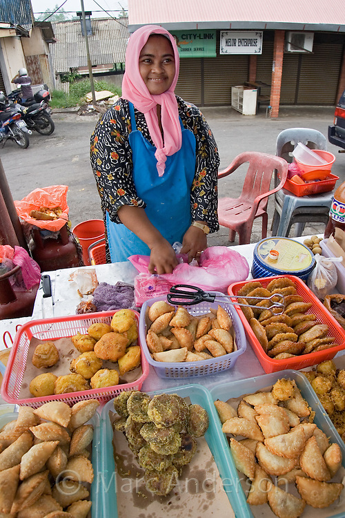 A Malaysian woman selling hot food at a market in Malaysia...