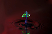 High-speed flash photograph liquid droplets using coloured light source. The droplet lands in the liquid and produces a coronet.