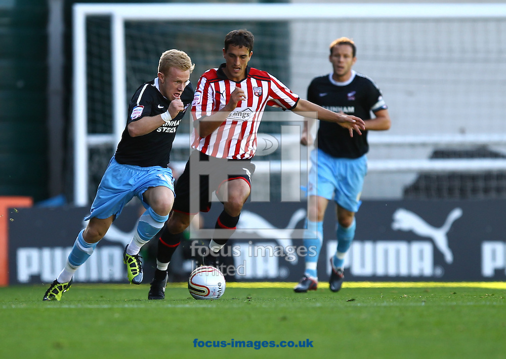 Picture by John Rainford/Focus Images Ltd. 07506 538356.15/10/11.. Craig Woodman of Brentford is outpaced by Mark Duffy of  Scunthorpe Utd the Npower League 1 match at Griffin Park stadium, London.