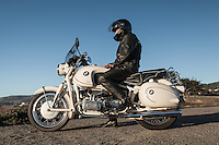 Brent Greenwood (MR) sitting on his 1960s BMW R60US motorcycle (PR) on a coastal road in Sonoma County.