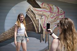 © Licensed to London News Pictures. 26/06/2018. Bournemouth, UK. Two visitors to Bournemouth Pier take a photograph in front of a mural depicting a melting ice cream in hot afternoon sunshine. Most of the UK is enjoying summer temperatures in the high 20's today. Photo credit: Peter Macdiarmid/LNP