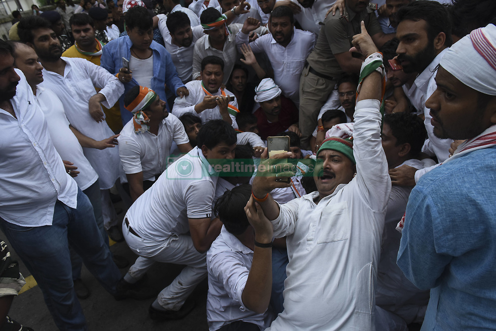 July 26, 2018 - New Delhi, India - An opposition Congress party worker takes a selfie as others shout slogans during a protest demanding from government to disclose the details of Rafale fighter planes deal and failure on platforms of unemployment, inflation, farmers, Dalits and women atrocities in New Delhi, India, July 26, 2018. (Credit Image: © Indraneel Chowdhury/NurPhoto via ZUMA Press)