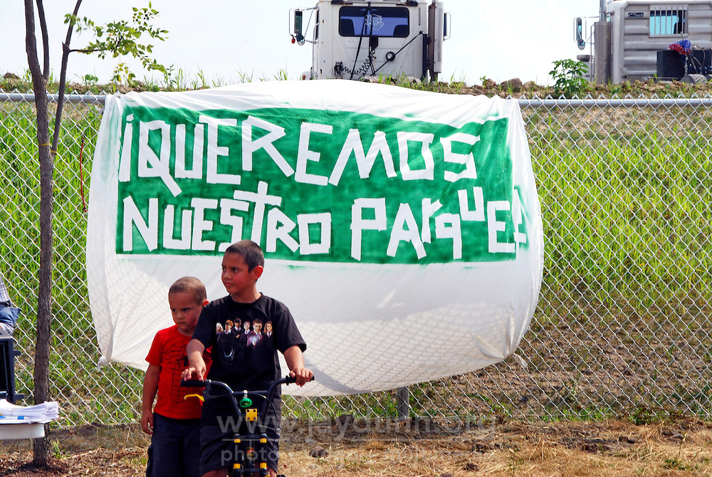 "USA, Chicago, August 25, 2009.   Children play next to a sign which reads ""We Want Our Park"" outside the Celotex clean-up site, possible home for much-needed open space. The Little Village Environmental Justice Organization, headquartered in a predominantly Mexican-American neighborhood of Chicago, campaigns not only against pollution but for clean power, park facilities, urban agriculture, and restoring public transit. LVEJO's staff and volunteers make significant outreach and education efforts, especially for youth. Photo for an HOY feature story by Jay Dunn."
