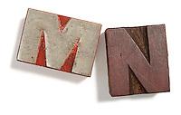 Letterpress typeset M and N print blocks on white background