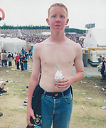 Young topless man holding a cup of ice cream and looking directly at camera.