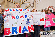 """15 JANUARY 2012 - PHOENIX, AZ:    Family members react as homecoming soldiers march into the hangar at the The 161st Air Refueling Wing of the Arizona Air National Guard in Phoenix. About 100 soldiers of A (Alpha) Company of the 422nd Expeditionary Signal Battalion (referred to as """"Alpha 4-2-2"""") of the Arizona Army National Guard returned to Arizona on Sunday, Jan. 15, following a nearly year-long deployment to Afghanistan. More than 10,000 Arizona Army and Air National Guard Soldiers and Airmen have been ordered to federal active duty in support of Operations Noble Eagle, Enduring Freedom, Iraqi Freedom, and New Dawn since September 2001. Approximately 200 Arizona National Guard Soldiers and Airmen are still serving on federal active duty overseas.  PHOTO BY JACK KURTZ"""
